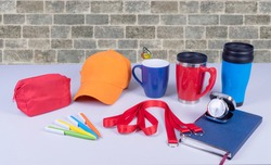 Composition of different promo products with rich colors -Thermo mugs, Lanyards Neck Strap, pens, mug, silver table office clock, zipped coin purse fabric, notebook,cap On desk grey and background gre