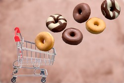 Composition of different types of donuts falling into a shopping cart. Fat food concept. Sweet food.