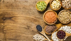 composition of dry legumes of different types, color and flavor on rustic wood background