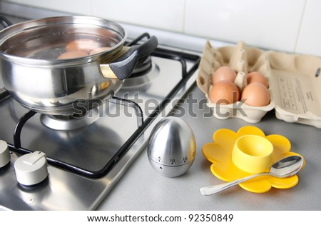 composition of eggs, stew pan, egg shape timer, eggcup end eggcartoon in the kitchen - stock photo