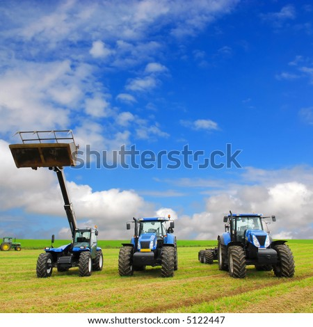composition of farming machinery on farmland with blue sky background