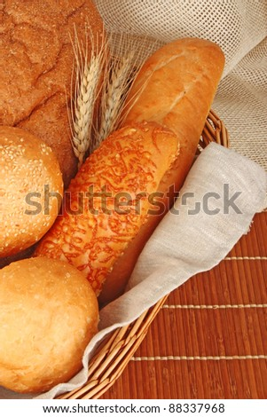 Composition of fresh bread and bakery in basket with ear of wheat, foodstuffs