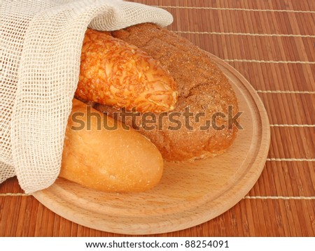 Composition of fresh bread and bakery with burlap on wood, foodstuffs