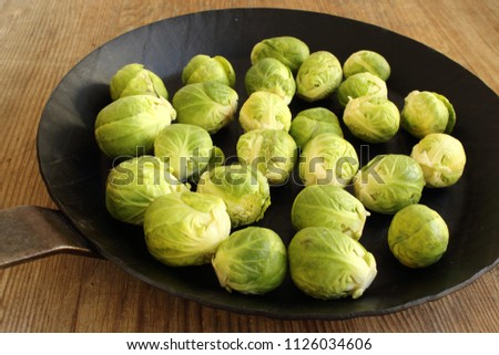composition of fresh brussels sprouts in an iron pan on a wooden board