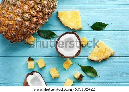 Composition of fresh coconut and pineapple on color wooden background #603132422