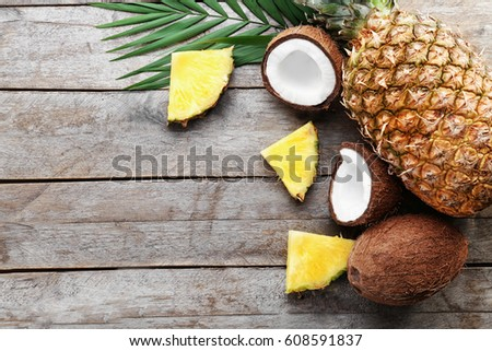 Composition of fresh pineapple and coconuts on wooden background #608591837