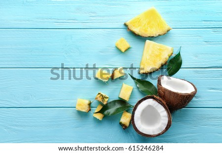 Composition of fresh pineapple slices and coconut on color wooden background #615246284