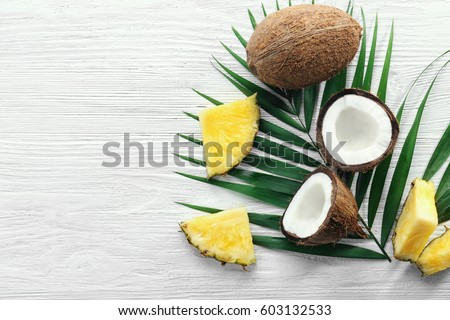 Composition of fresh pineapple slices and coconuts on light wooden background #603132533