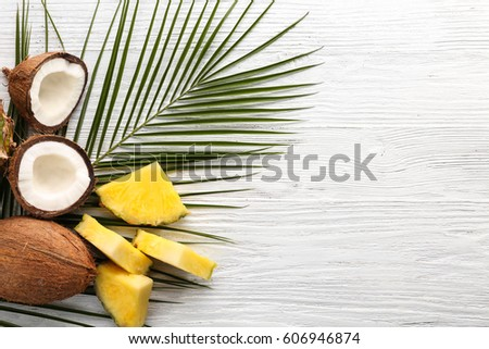 Composition of fresh pineapple slices and coconuts on light wooden background #606946874
