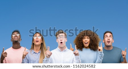 Composition of group of friends over blue blackground amazed and surprised looking up and pointing with fingers and raised arms.