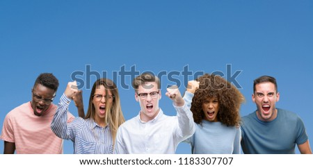 Composition of group of friends over blue blackground angry and mad raising fist frustrated and furious while shouting with anger. Rage and aggressive concept.