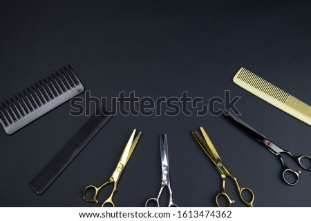 Composition of hairdressers instruments on black textured background. Top views clear space