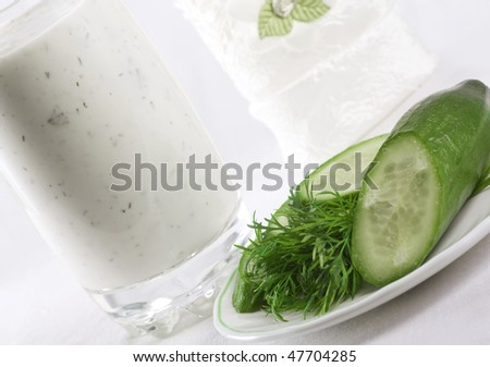 Composition of kefir in the glass with cucumber and dill near on the plate