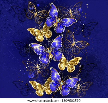 Composition of luxurious sapphire and gold jewelry butterflies on blue textured background.  ストックフォト ©