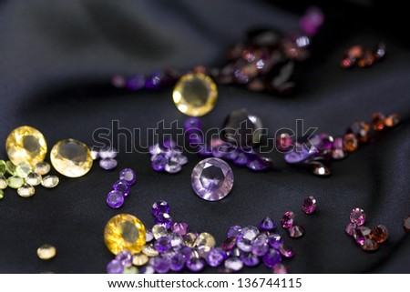 Composition of mixed colorful faceted gemstones on black background