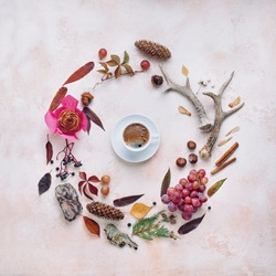 Composition of natural details with cup of coffee in the center on beige stone background with blank space for text; top view, flat lay