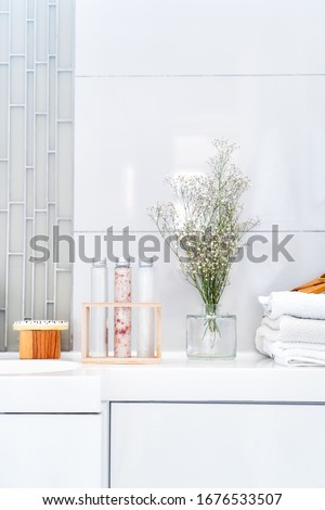 Composition of natural spa treatment for body - scrab, gel, cream, bath salt, massage brush, towels and fesh flowers on white bathroom background. Vertical card, copy space