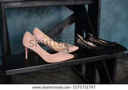 composition of pink and black women s shoes standing on a black stool against a blue cement wall. #1575731797