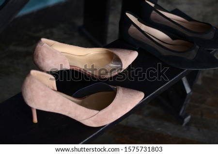 composition of pink and black women s shoes standing on a black stool against a blue cement wall. #1575731803