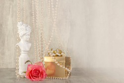 Composition of pink rose flower, gift and statuette or figurine. Greeting card mock up