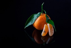 Composition of ripe delicious and beautiful Tangerines with green leafs. Peeled Mandarine orange and Tangerine orange slices on a Dark reflective surface.