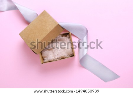 Composition of sexy lace woman lingerie in craft box with silver ribbon.Pink background,top view.Fashion trend romantic lingery. #1494050939
