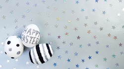 Composition of silver glitter inscription Happy Easter on a white egg and metallic stars spangles sequins. Eggs with black and silver lines and polka dots. Flat lay, top view, close up, copy space