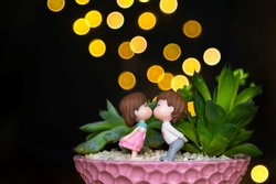 Composition of succulents and mini-sculptures of a girl and a boy kissing or in love. Yellow bokeh on a dark background. Day of Happiness