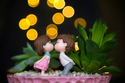 Composition of succulents and mini-sculptures of a girl and a boy kissing or in love. Yellow bokeh on a dark background. Day of Happiness. Valentine`s day