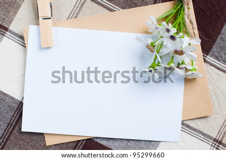 composition of the empty cardboard card with flowers and an envelope on fabric