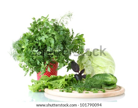 Composition of various herbs on a cutting board and a red cup with white polka dots isolated on white