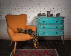 Composition of vintage orange armchair, blue cabinet and ornate scarf in studio