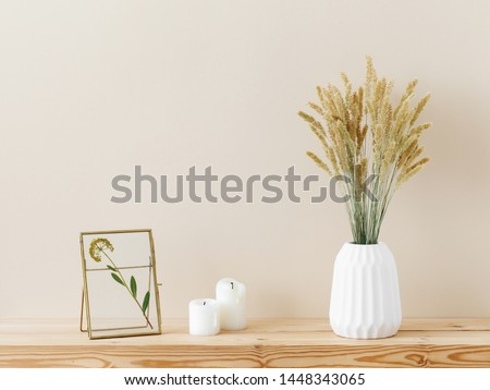 Composition of white ceramic vase with bouquet of dry spikelets, golden photo frame with dried flower, candles on wooden table on pastel beige background. Stylish home decor. Modern interior design.