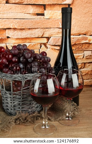 composition of wine,basket and grapes on table on brick wall background