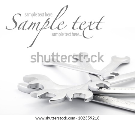 composition of wrenches on white background (with sample text)