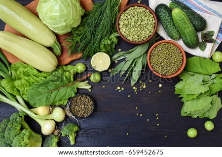 Composition on a dark background of green organic vegetarian products: green leafy vegetables, mung beans, zucchini, garlic, onions, cucumbers, peppers, lime. Top view. Green food #659452675