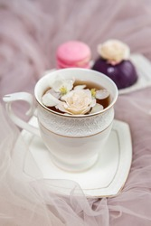 Composition on a light background: tea with flower petals, sweets and flowers. Still life with flowers and fruit tea