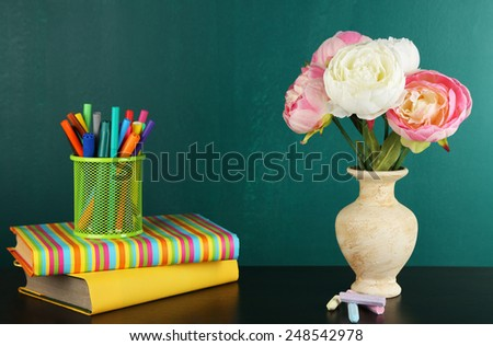 Composition on desk with books and flowers on green blackboard background