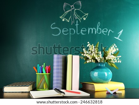 Composition on desk with books and flowers on green blackboard with inscription on background