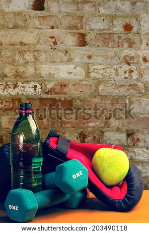 Composition presenting healthy lifestyle,with green apple,boxing gloves,bottle of water and dumbbells,against wall background.