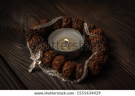 composition symbols of faith, focus on a burning candle, around it a Buddhist wooden bracelet intertwined with a Christian cross on a chain. religious freedom day #1555634429