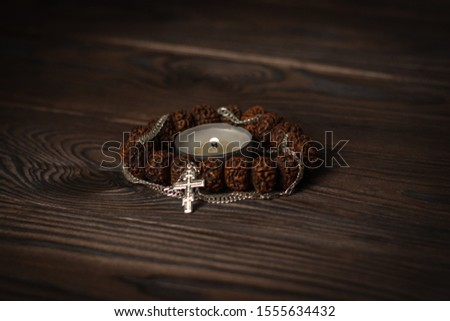 composition symbols of faith, focus on a burning candle, around it a Buddhist wooden bracelet intertwined with a Christian cross on a chain. religious freedom day #1555634432