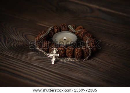 composition symbols of faith, focus on a burning candle, around it a Buddhist wooden bracelet intertwined with a Christian cross on a chain. religious freedom day #1559972306