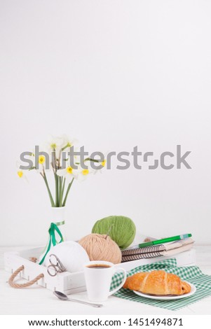 Composition with a vase and a wooden tray and balls of yarn for needlework. Morning needlewoman, breakfast, comfort, hobbies, knitting