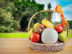 Composition with assorted fruits in wicker basket on wooden table, at blurry agriculture field on farm land in summer background and copy space