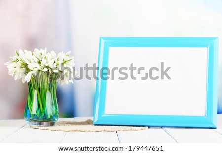 Composition with beautiful snowdrops in vase, photo in frame on wooden table on bright background