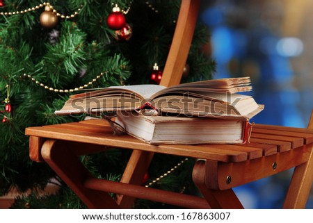 Composition with books on chair on Christmas tree background