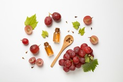 Composition with bottles of natural grape seed oil on white background, top view. Organic cosmetic