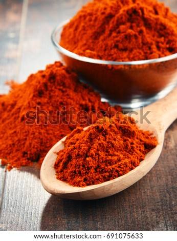 Shutterstock Composition with bowl of chili powder on wooden table.