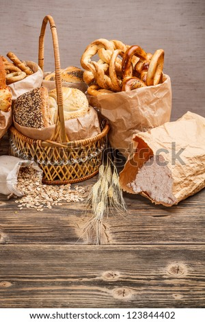 Composition with bread and rolls in wicker basket and paper bag